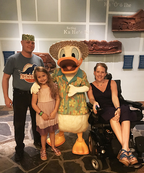 a man in a grass hat and silly smile, a little girl, Donald Duck in a Hawaiian shirt, and a lady in a wheelchair smiling.