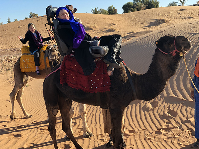 two camels in the desert, one in the foreground with a special accessible saddle and a woman on it, another in the background with a little girl on it
