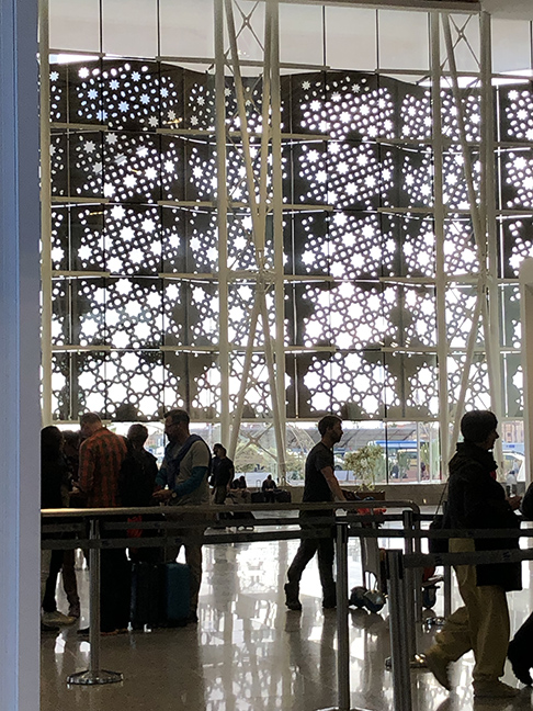 a picture of a huge screen across a window pierced with geometric patterns in an airport