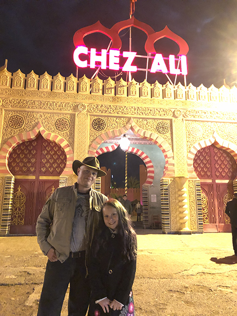 a girl and her father in front of a fanatical Moroccan building with a red neon sign on top that says Chez Ali