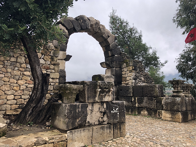 A ruined Roman arch with trees on each side