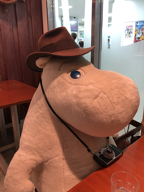 a giant stuffed Moomin stuffy with a brown fedora and camera on