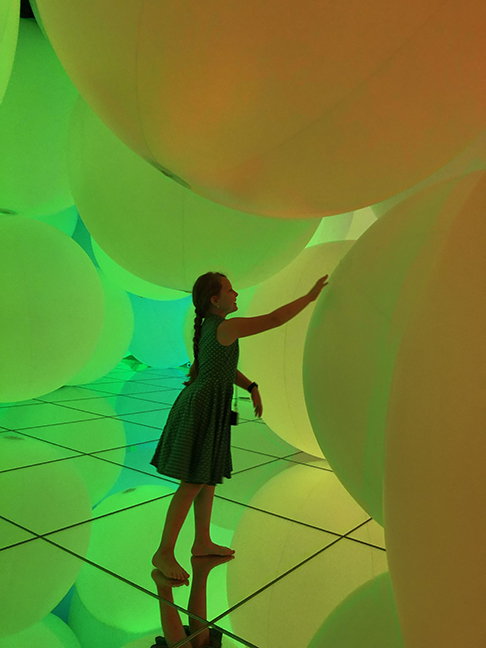 a girl touching a giant green ball in a room of giant green and yellow balls