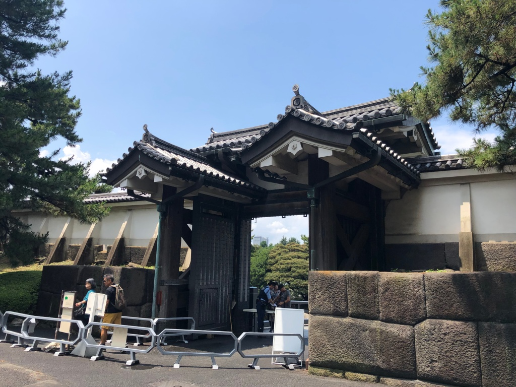 a large feudal Japanese gate with large blocks of stone in a wall to the sides of it