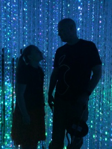 silhouettes of a little girl and a man with thousands of sparkling blue and green lights behind them hanging by strings.