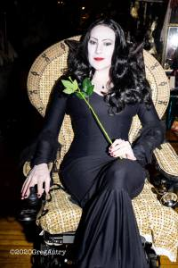 a woman dressed as Mortica Addams (black wig, tight long black dress, headless rose in hand) sitting in a wheelchair which has a covering designed to look like a ratan chair.