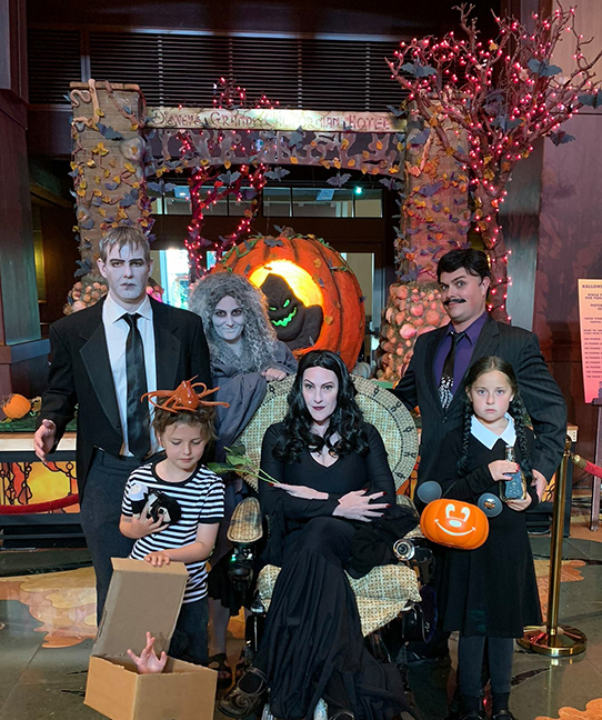 a family dressed as the Addams Family with  Lurch, Mama, Gomez, Morticia  seated in a chair, Wednesday, Pugsley,  and even Thing in a box in front of a giant pumpkin  with a carving of Oogie Boogie fromm Nightmare Before Christmas.