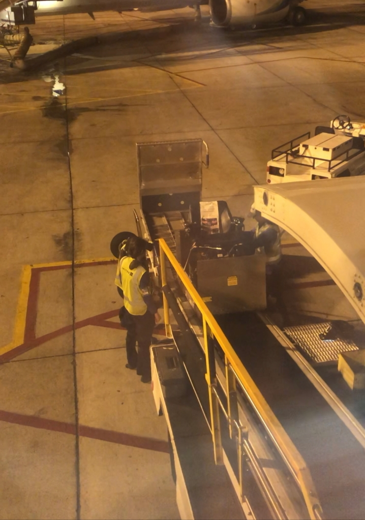a wheelchair is being taken up a conveyor belt onto a plane