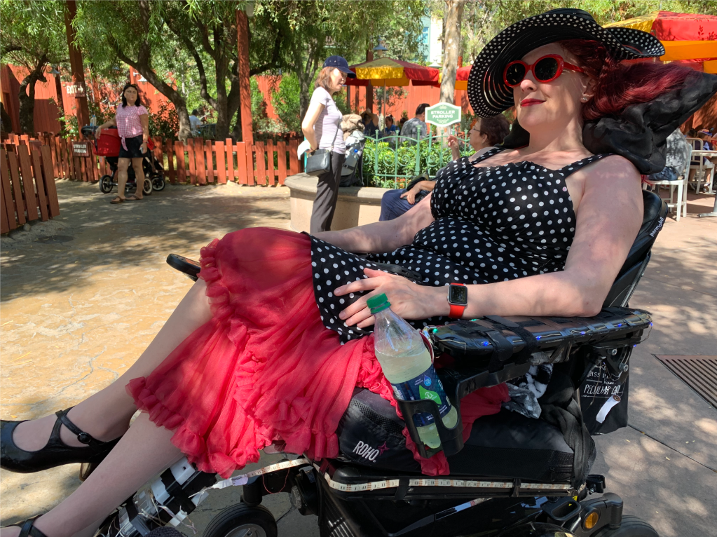 a woman in a black dress with white polka dots and a red petticoat, red sunglasses, red watch and black sun hat reclining in a wheelchair.