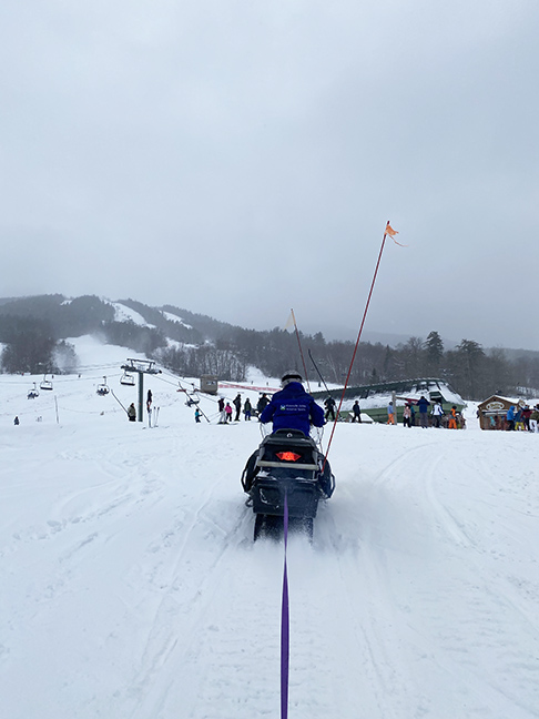 a snowmobile towing the person taking the picture by a long piece of purple webbing with a snow covered ski slope in the background