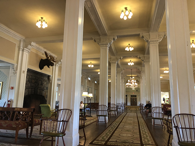 a huge hotel lobby with wooden white pillars going into the distance
