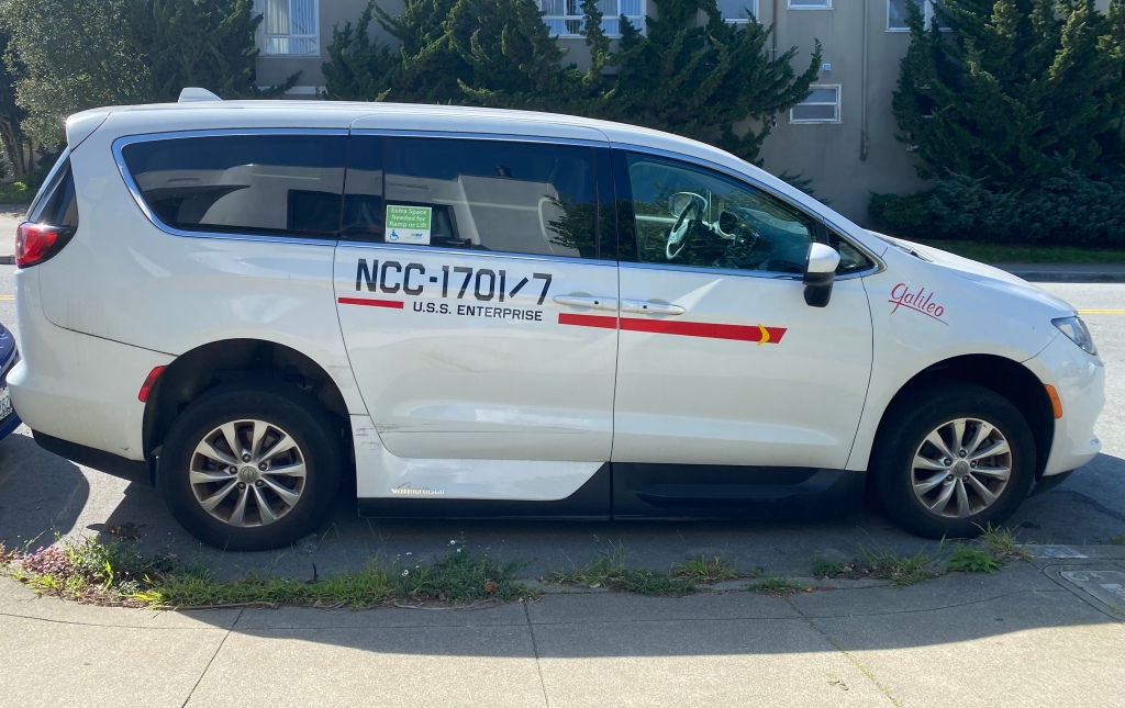 a white wheelchair van with stickers on it that make it look like a Star Trek Galileo shuttle