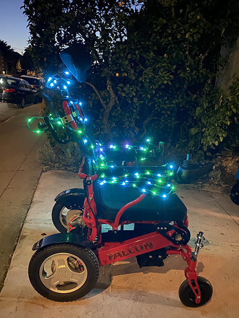 A red wheelchair in twilight with many green and blue LEDs on the arms and back of the chair.