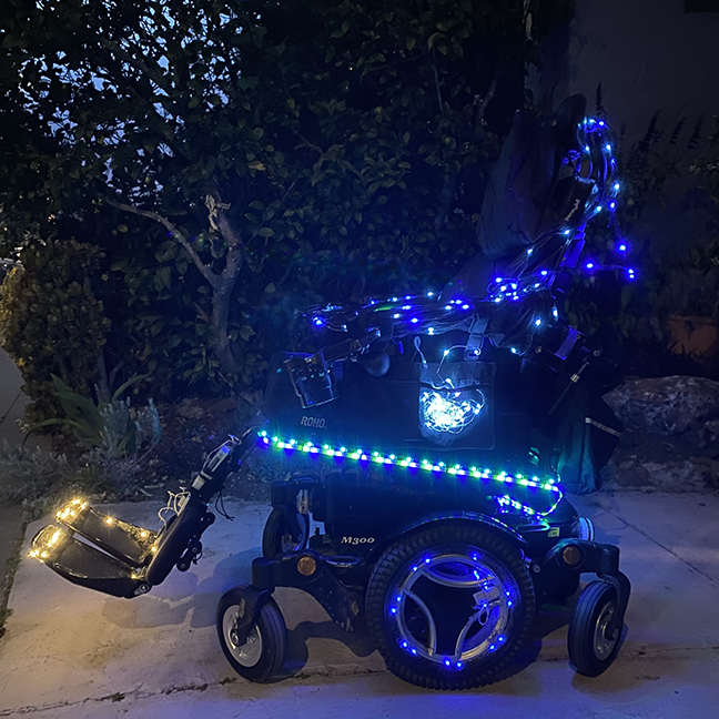 A wheelchair in the dark lit with lots of blue and blue/green LED lights.