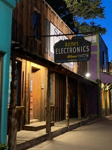 """an old wooden beam porch on and old west style building with a sign hanging over it saying """"Arches Electronics"""""""