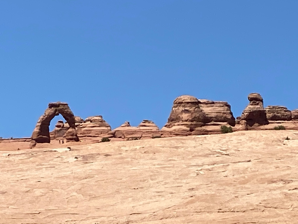 a series of orangish rocks with and arch of rock to the left