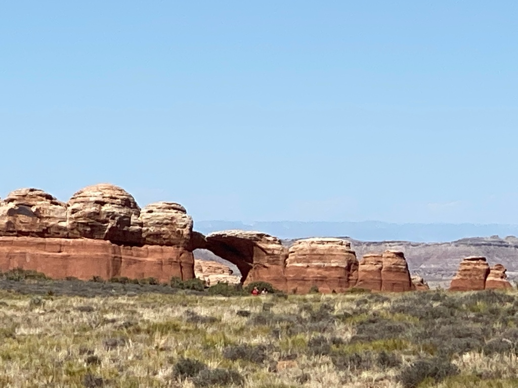 arch of orangish rock out across a field, pale blue sky.