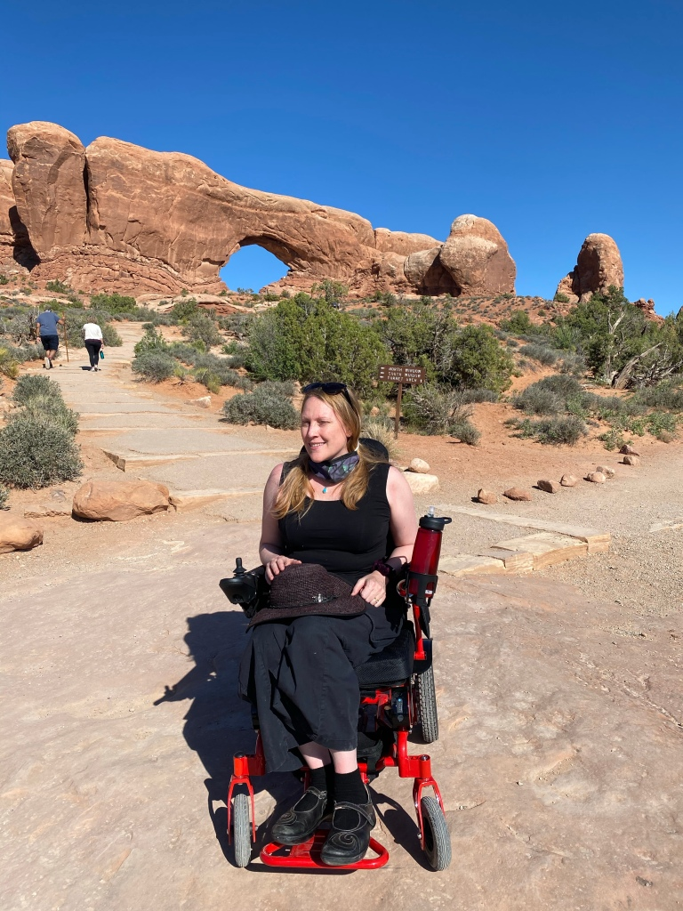 image of a blonde woman in black in a red wheelchair with an arch of reddish rock behind her.