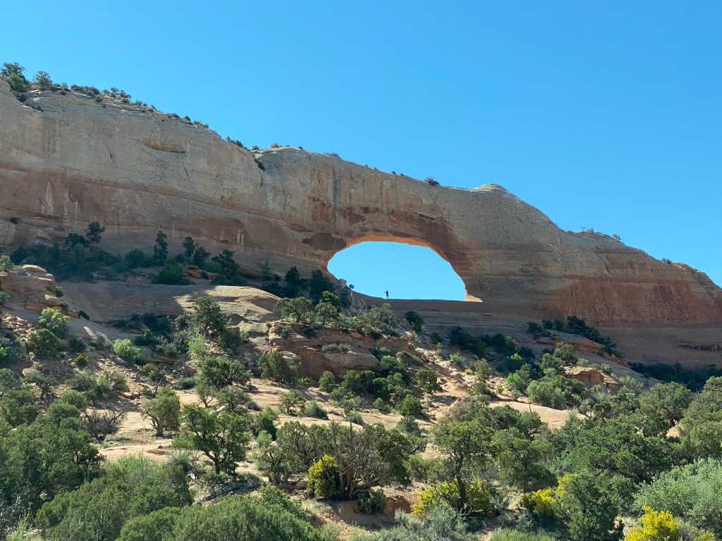 an arch of peachy/tan rock on a hill with shrubs, light blue sky.  Tiny person under it in the distance .