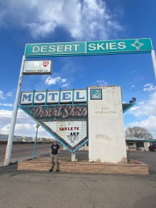 """Man standing in front of an old faded neon sign which reads """"Desert Skies Motel"""""""