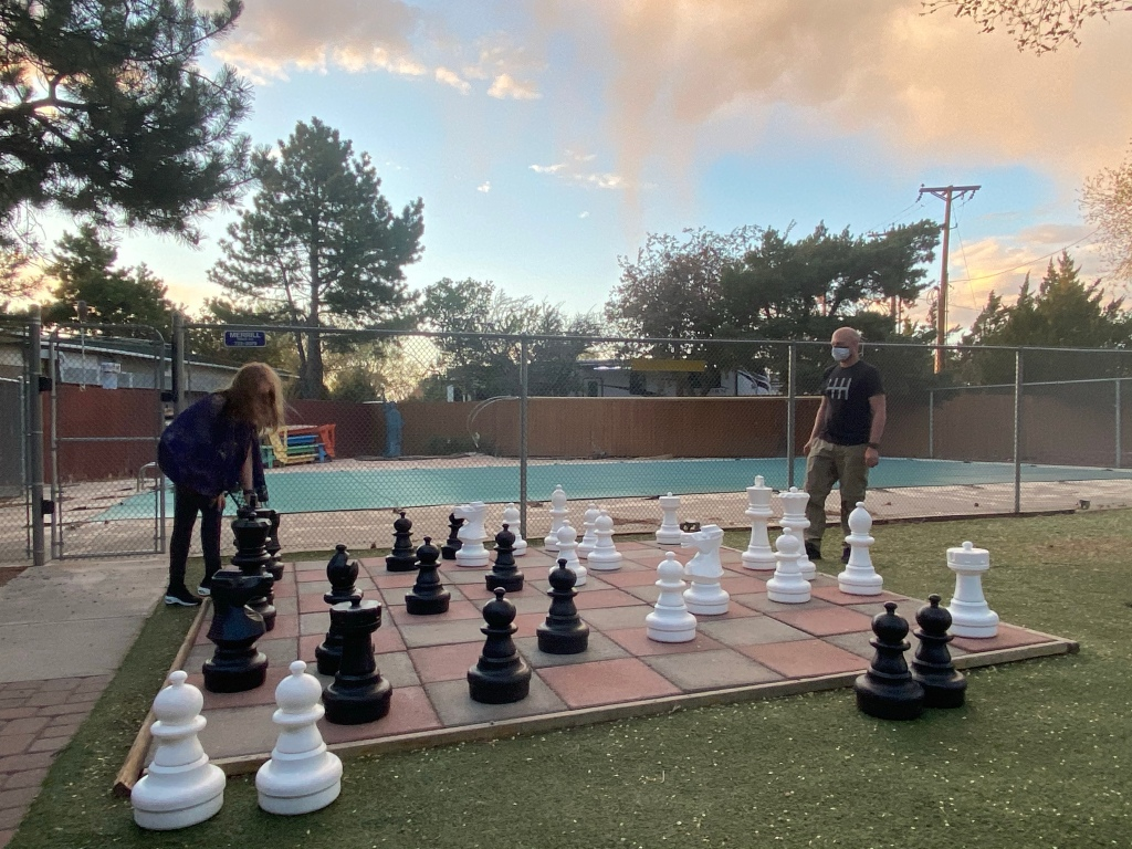 A kid and a man playing a giant chess set together.